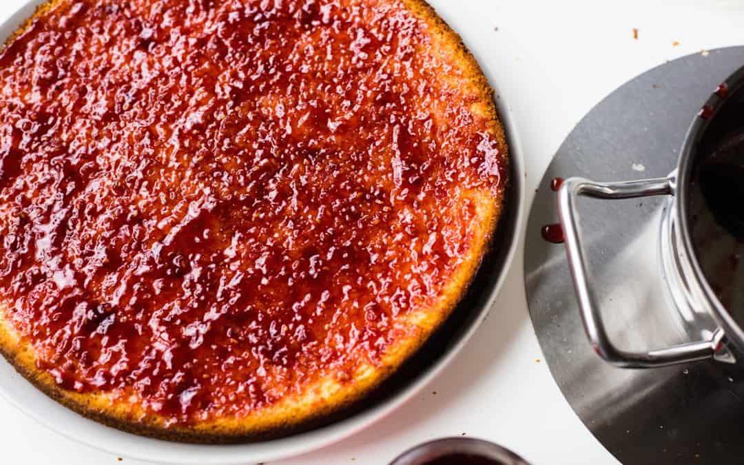 Ein Kuchen ist mit einer Marmeladenschicht bestrichen. Daneben steht ein kleiner Topf.