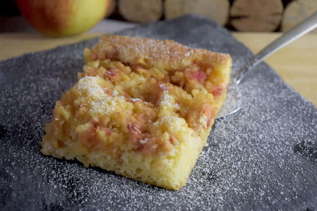 Nahaufnahme eines Stücks Apfe-Blechkuchen mit Kuchenheber