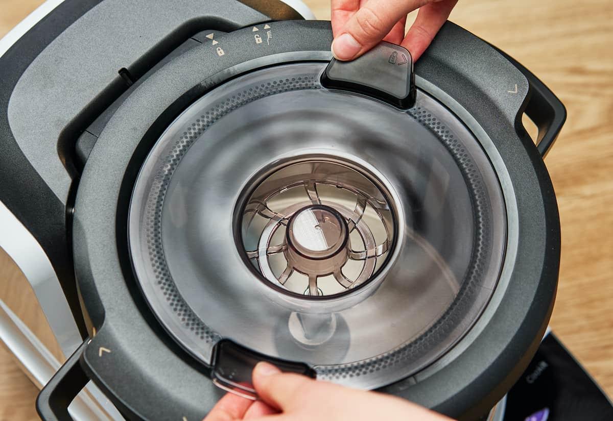 Hände entnehmen Deckel des Bosch Cookit Topf. –Foto: PR