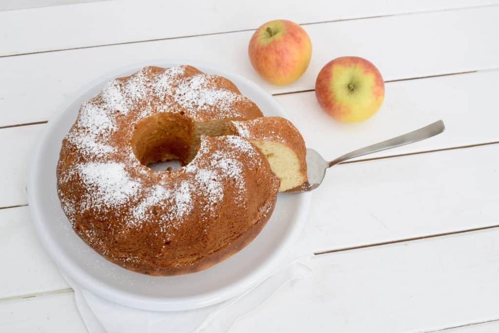 Apfelmuskuchen in Gugelhupfform auf weißem Holzuntergrund mit zwei Äpfeln daneben