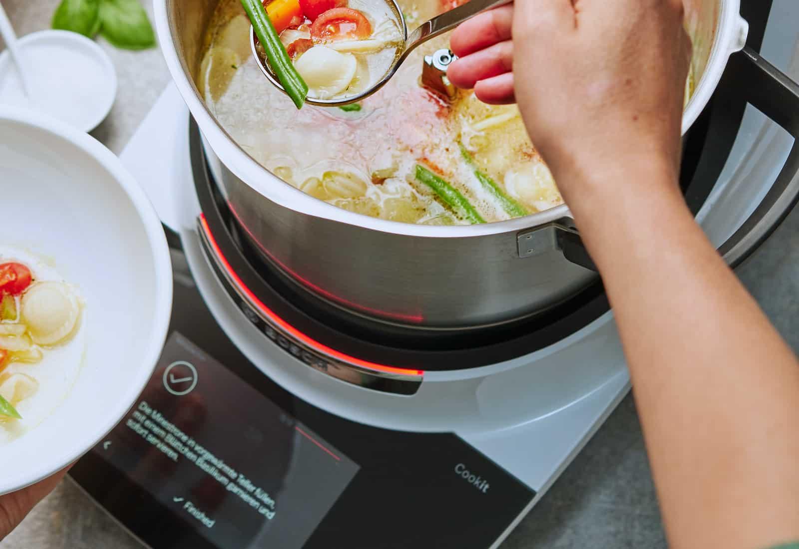 Hand serviert Suppe mit aus Cookit Topf. – Foto: PR