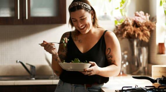 Tättowierte Frau in hemischerKüche mit Salatschüssel in der Hand