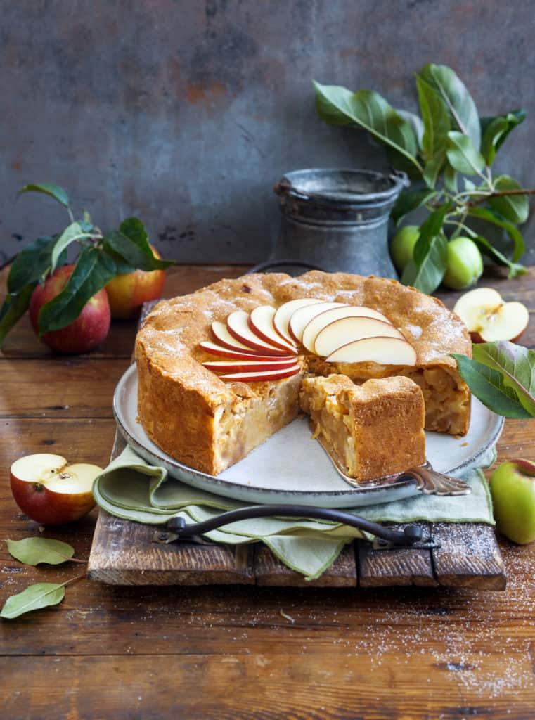 Angeschnittener gedeckter Apfelkuchen auf weißem Teller mit Tortenheber